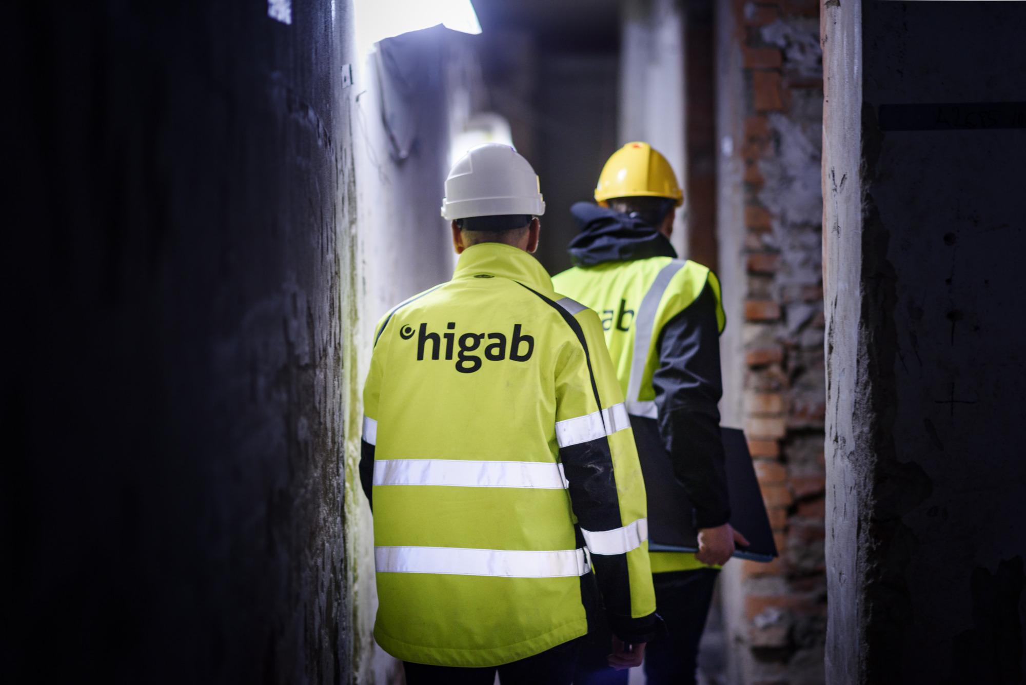 Två män i reflexjackor går på en byggarbetsplats.