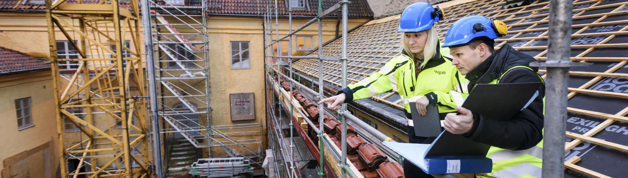 Två Higab-medarbetare tittar ut över byggarbetsplats.