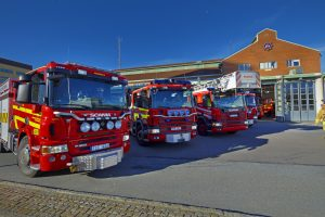 Brandbilar står parkerade utanför brandstation.
