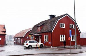 Rött trähus med bil parkerad framför