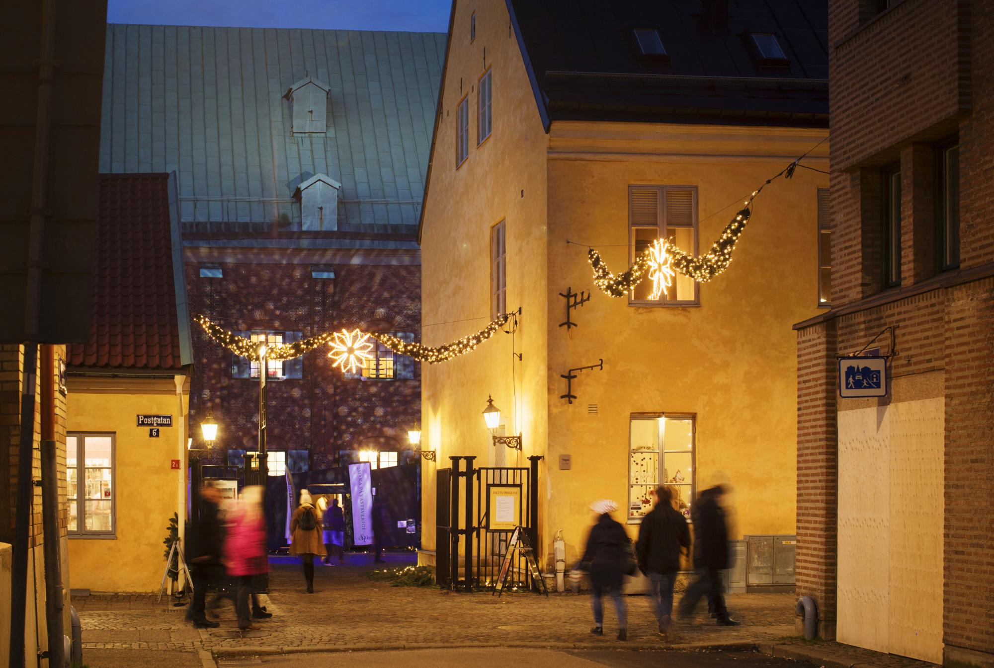Människor i rörelse framför ett julpyntat Kronhuset & Kronhusbodarna.