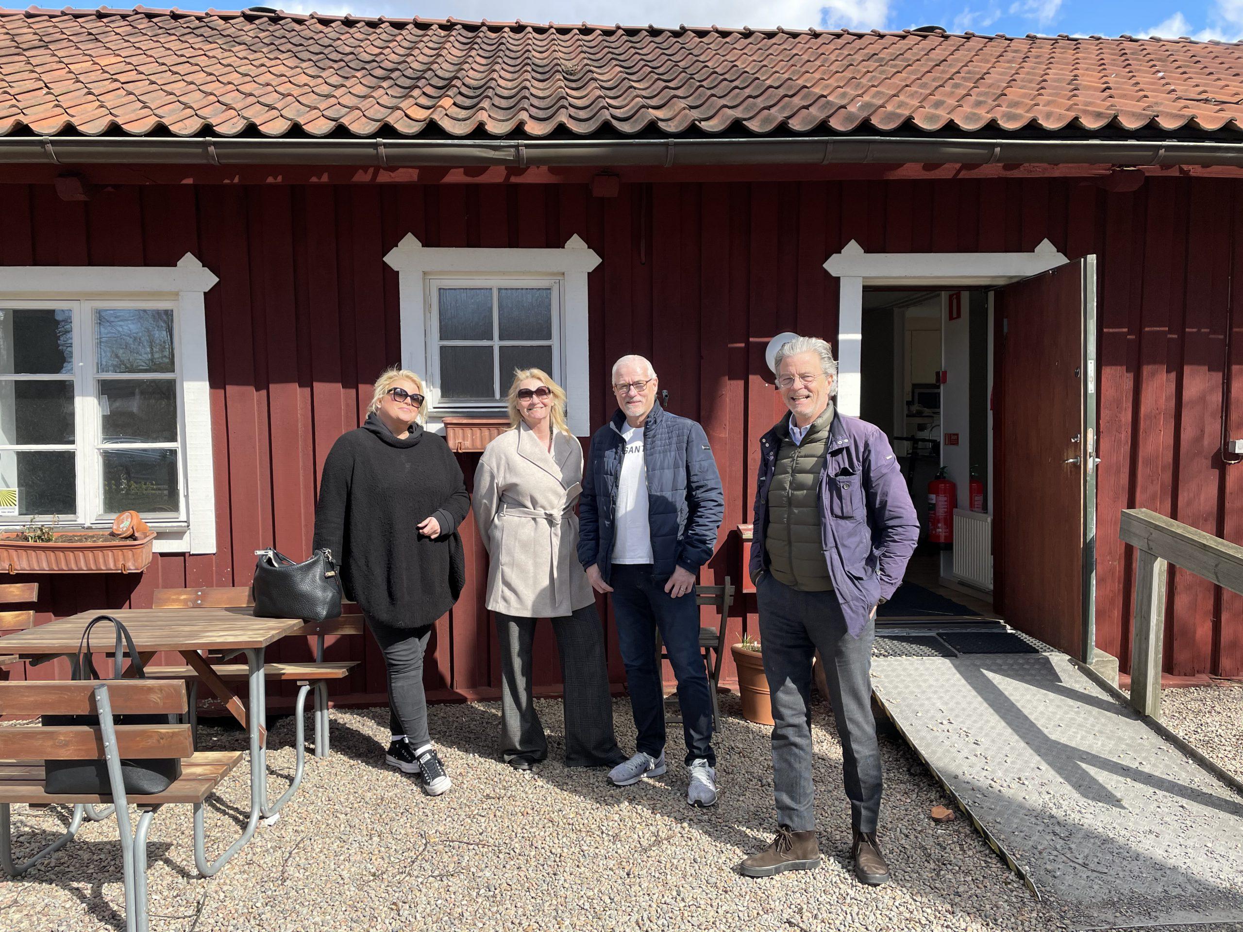 Fyra personer står framför ett lågt trähus