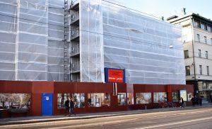 Inklädd byggnadsställning och byggplank framför Börsen på Östra Hamngatan