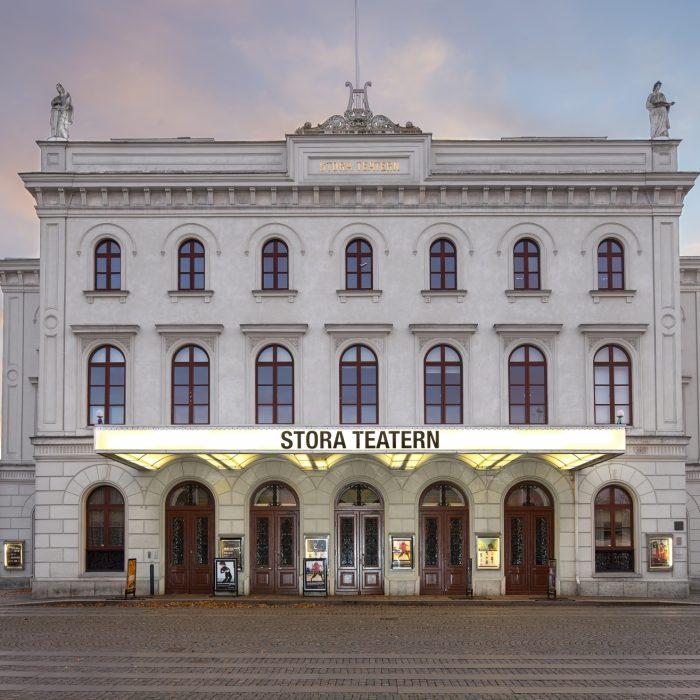 Framsidan av den vita stenbyggnaden Stora Teatern under kvällstid.