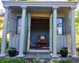 En blå träpaviljong med pelare och öppen dörr