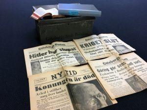 Fyra gamla tidningar ligger på golv.