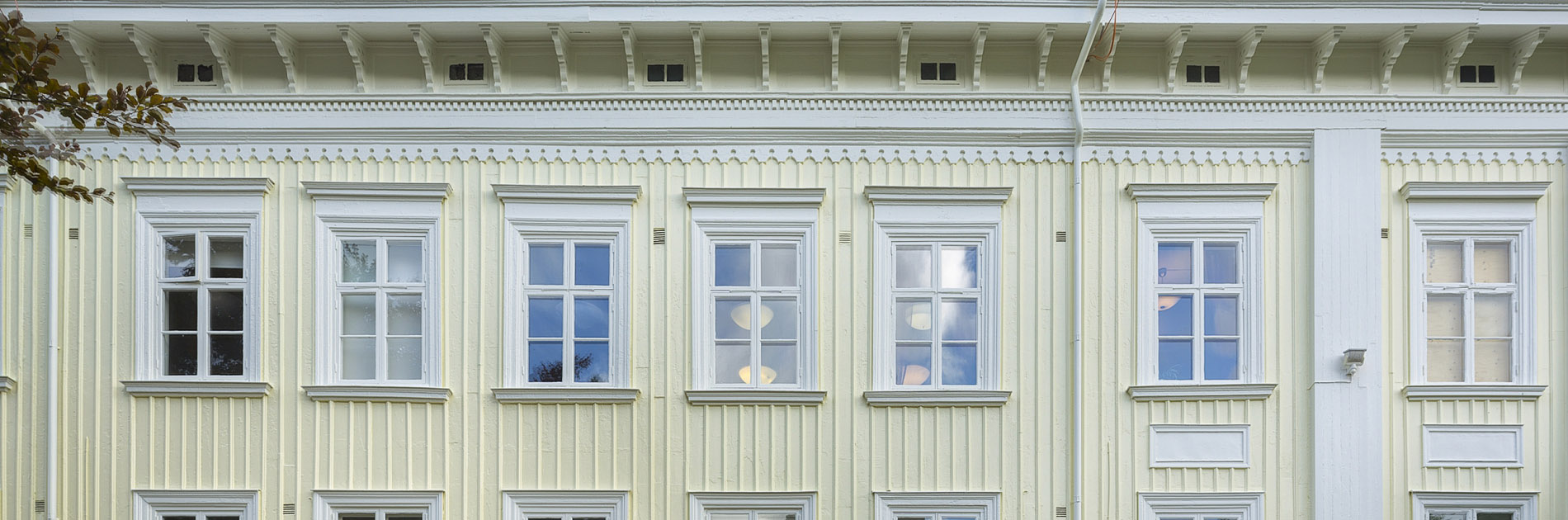 Bö Herrgårds ljudagula träfasad med vita fönster.