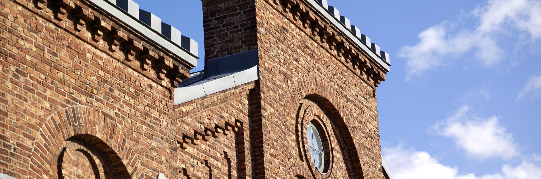 Närbild på Exercishusets röda tegelfasad och tak med tinnar.