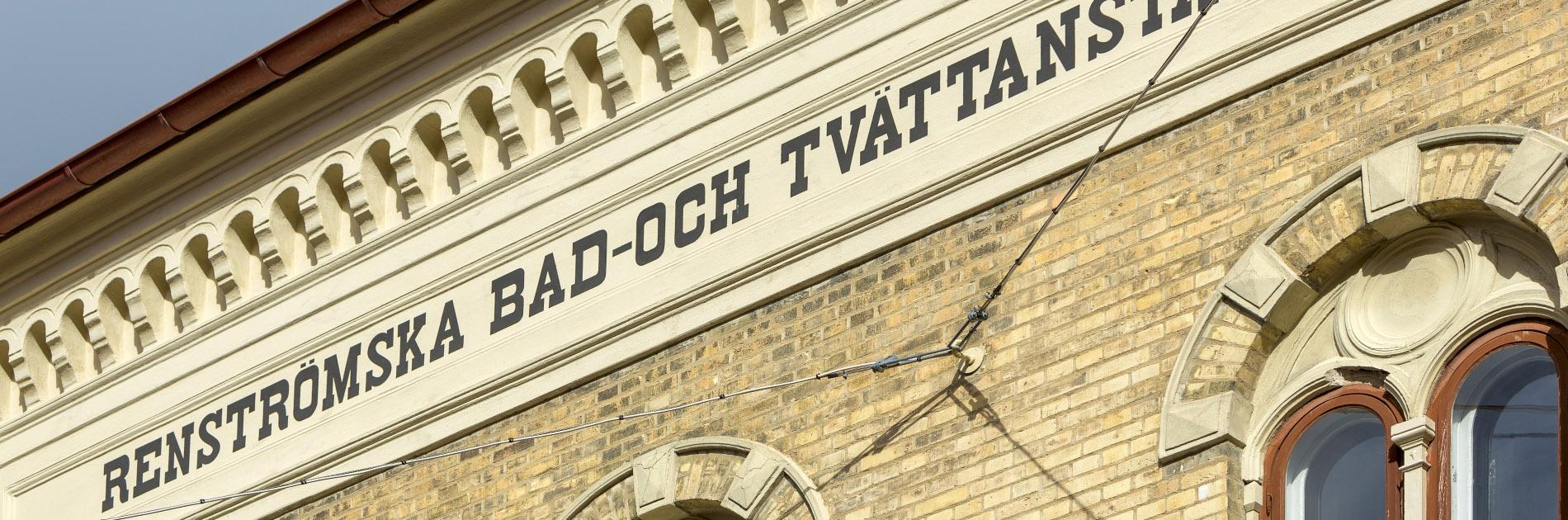 Fasadtext på Hagabadet där det står Renströmska Tvätt- och Badinrättningen.