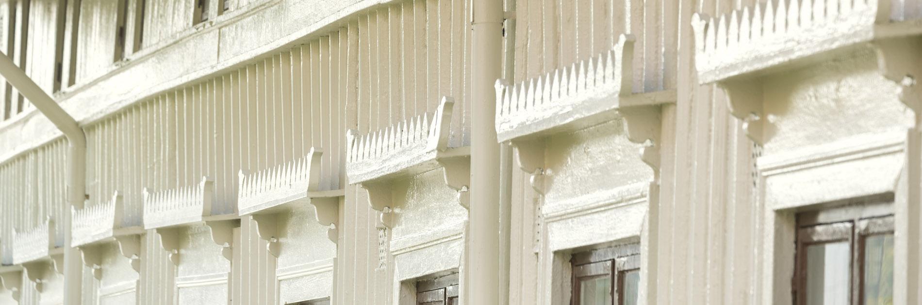 Vit träfasad med dekorationer ovanför fönstren.