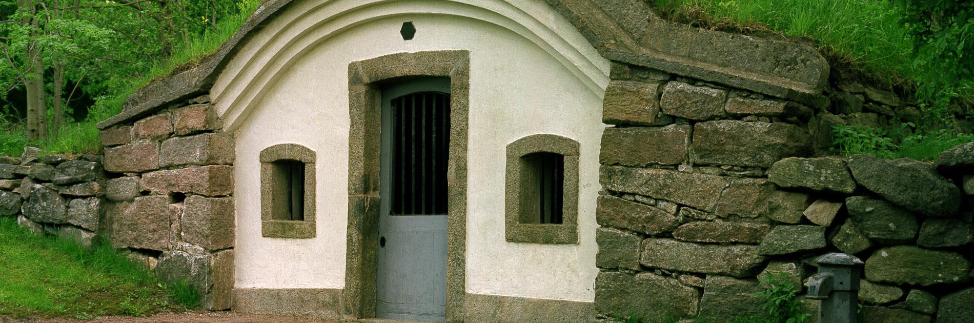 Äldre och mindre stenfasad med rundat tak, dörr och två små fönster vid Kallebäcks Källa.