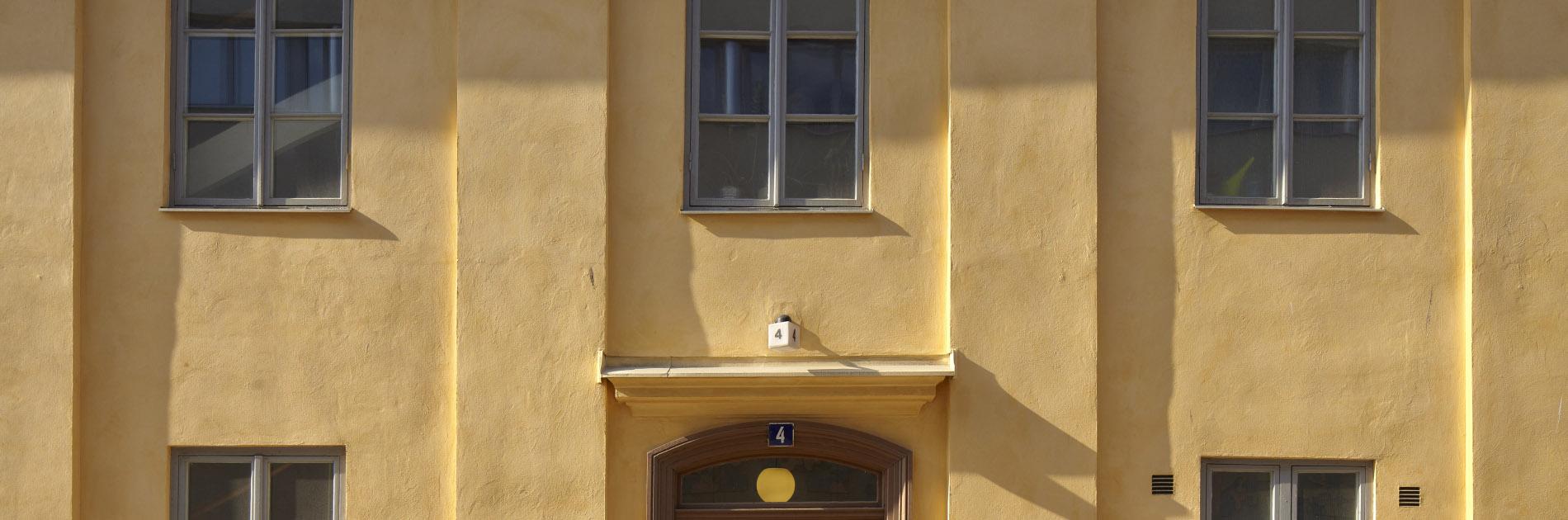 Utsidan av den gula stenbyggnaden på Postgatan 4.