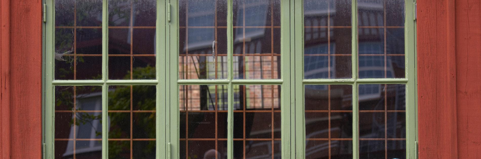 Äldre grönt fönster på en röd träbyggnad på Remfabriken.