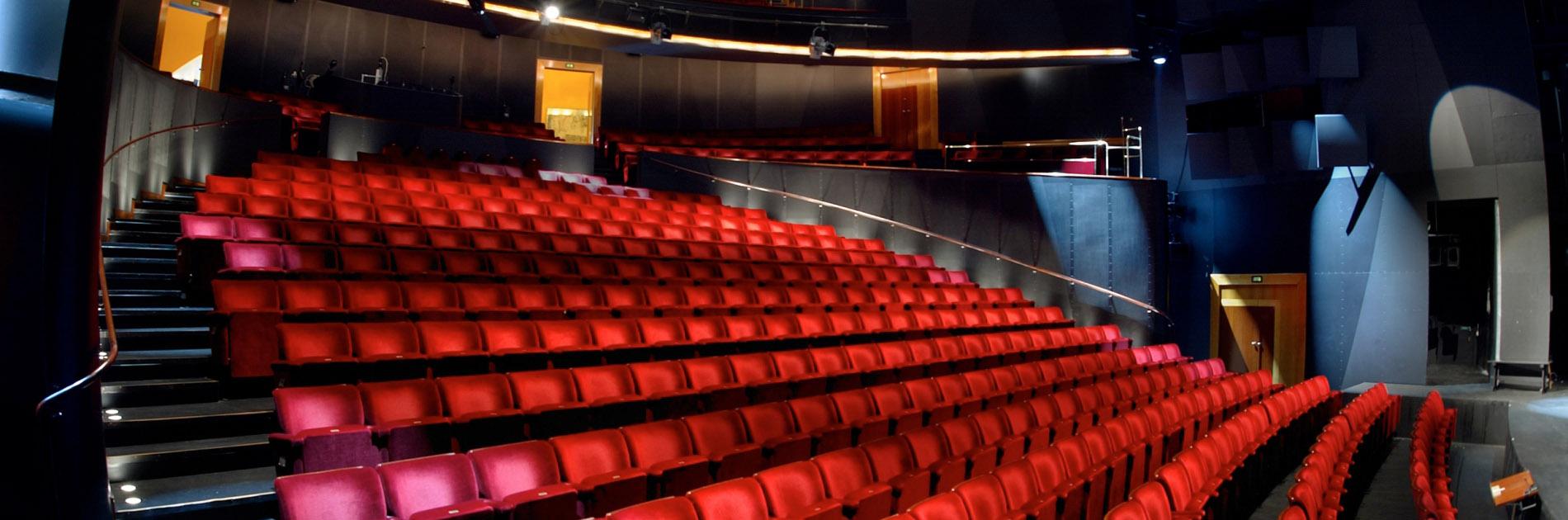 Bänkrader med röda stolar i Stadsteaterns salong.