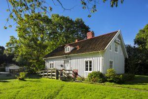 Utanför den grå träbyggnaden Vidkärrs Herrgård med grönska runt omkring.